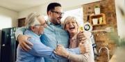 ouder echtpaar lacht met hun volwassen zoon terwijl ze elkaar omhelzen