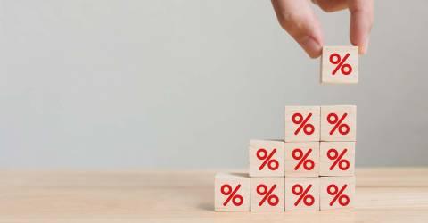 Hand die een houten kubusblok met percentage teken zet in opwaartse richting op dezelfde andere blokjes